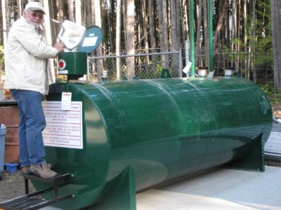 Photo of Graham MacDonald pouring used oil in GIRO's new doudle walled tank.